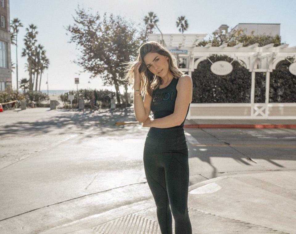 Erin posing outside wearing black Fendi tank top and black leggings and tennis shoes