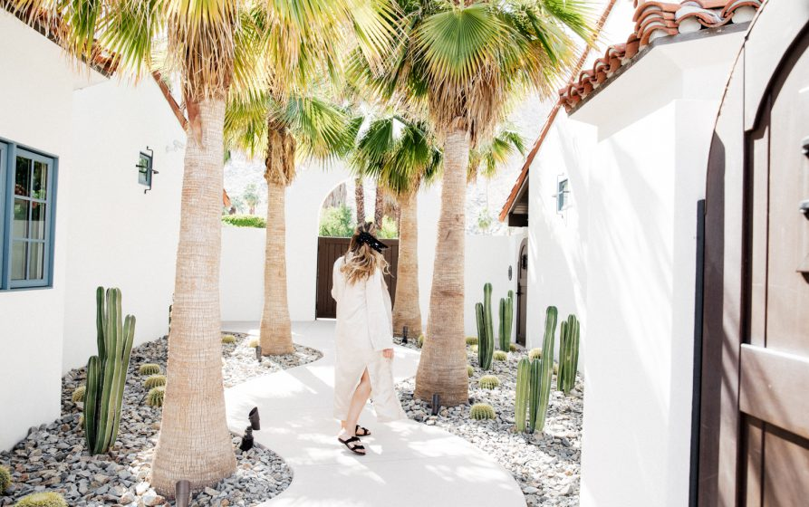 Erin walking in a bright courtyard with cacti and palm trees