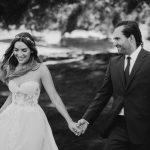 Erin and Matt in their wedding attire smiling and holding hands
