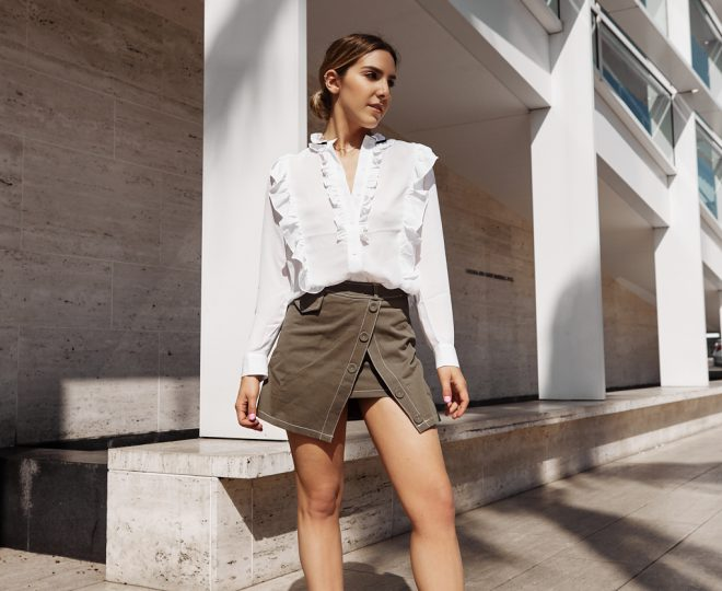 Erin posing while wearing a white blouse, tan skirt and red high heels with hair styled in a bun.