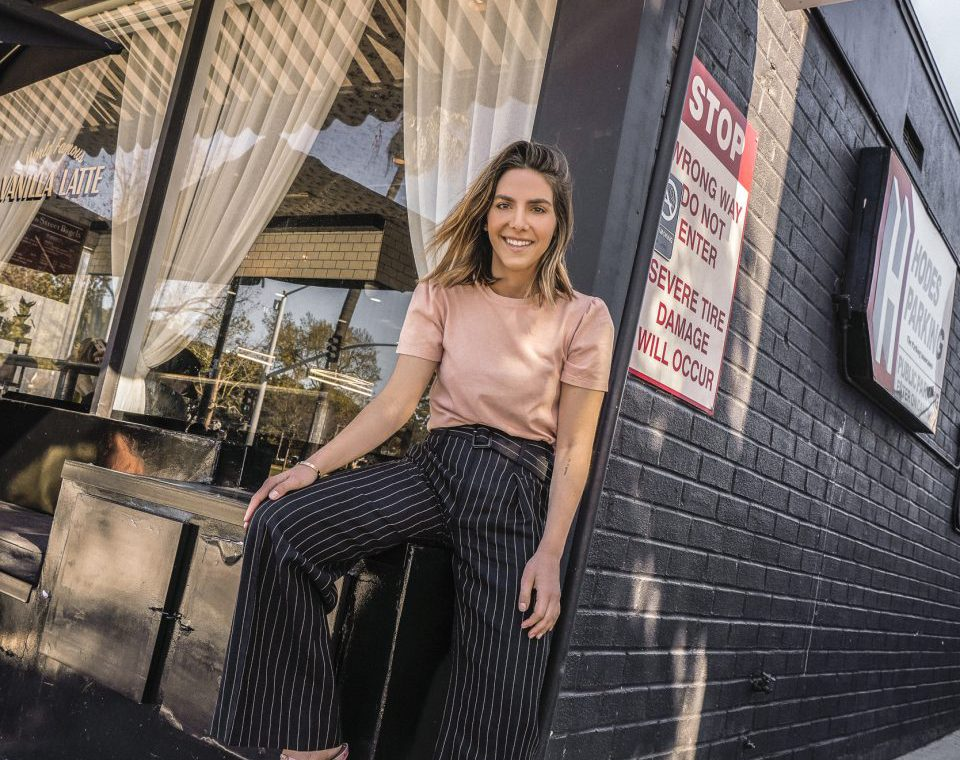 Erin posing outside a cafe with striped pants, a blush shirt, and pink heels on.