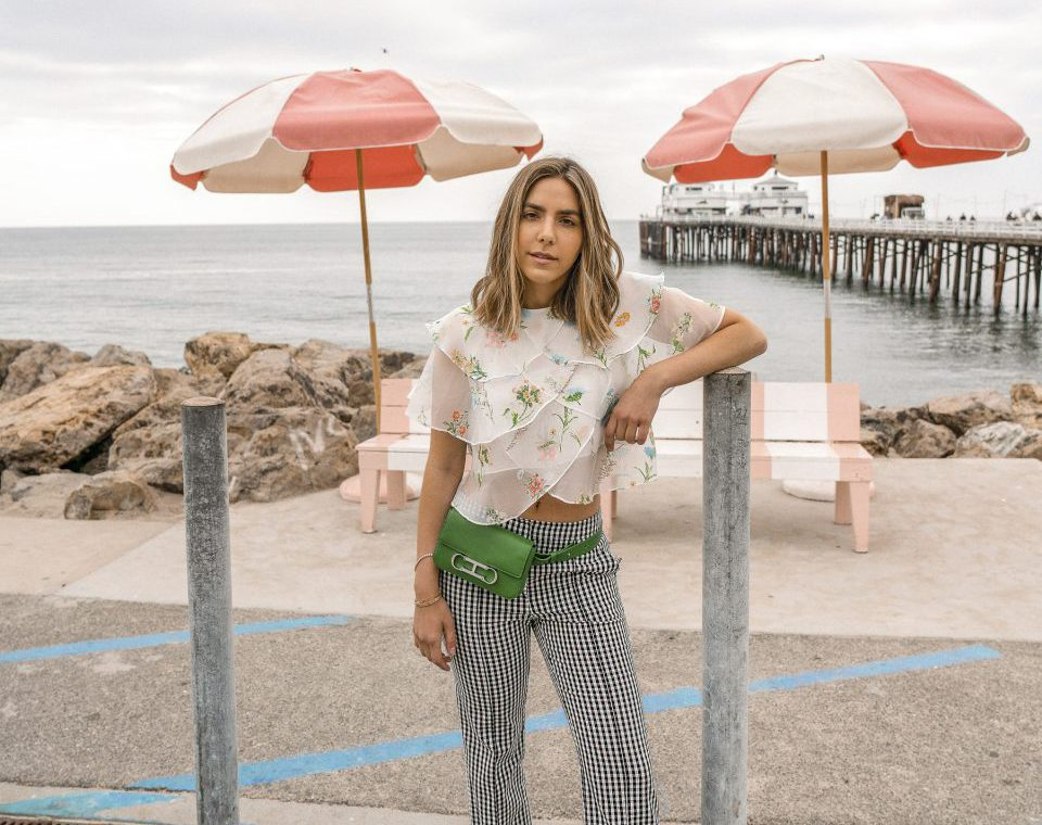 Erin in a floral blouse and checkered pants and a green fanny pack