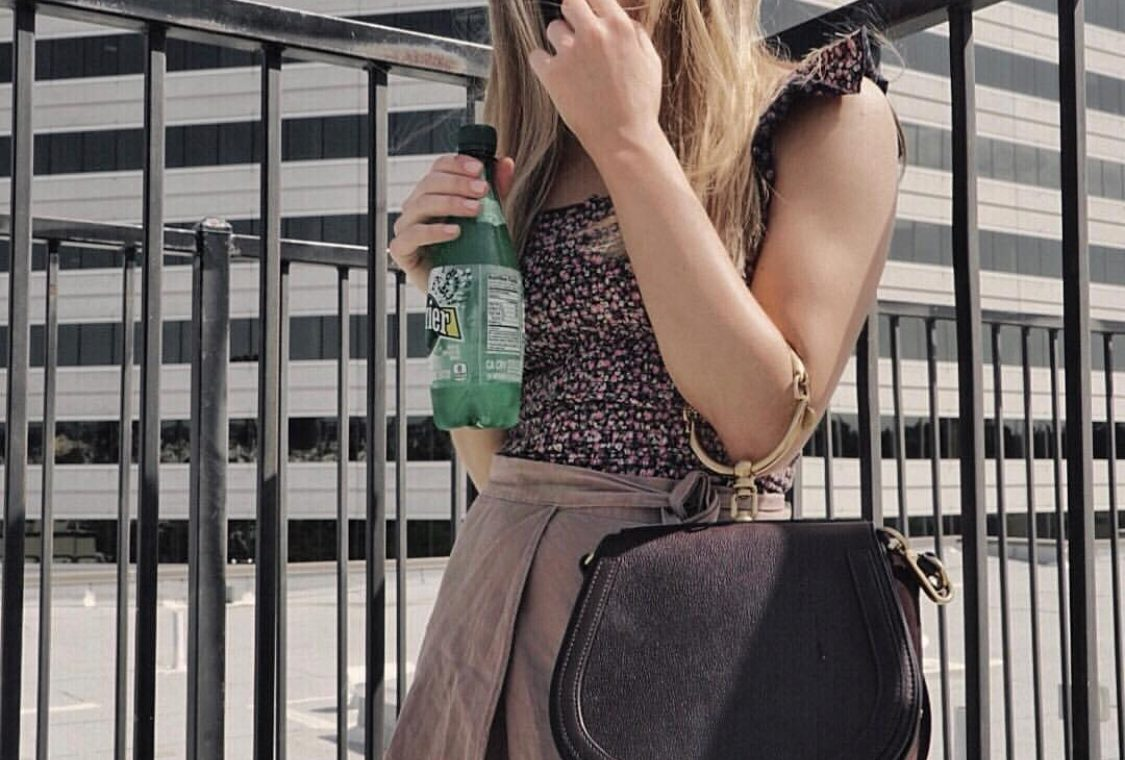 Erin standing outside in a dress holding a bottle of Perrier