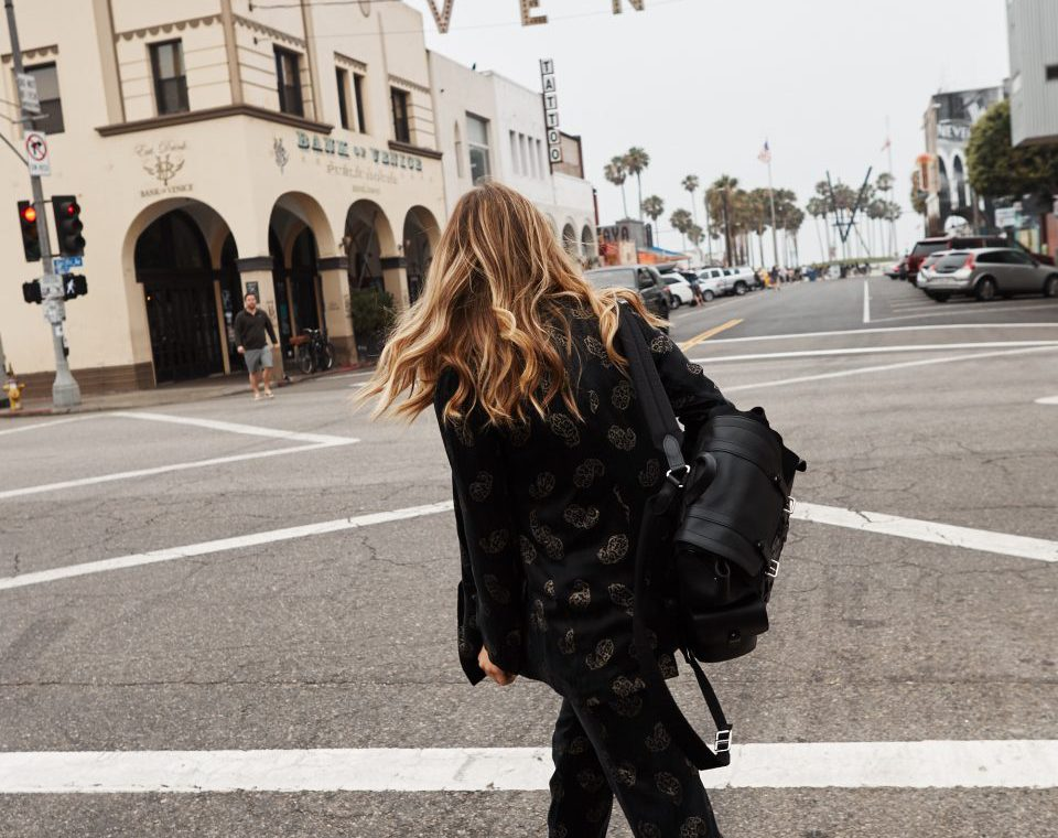 Erin crossing the street and wearing a patterned black suit with white sneakers and a black leather backpack
