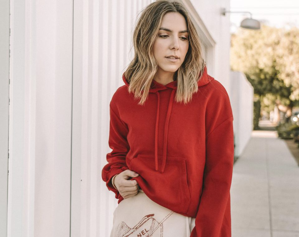 Erin wearing an oversized red hoodie and pink chanel skirt