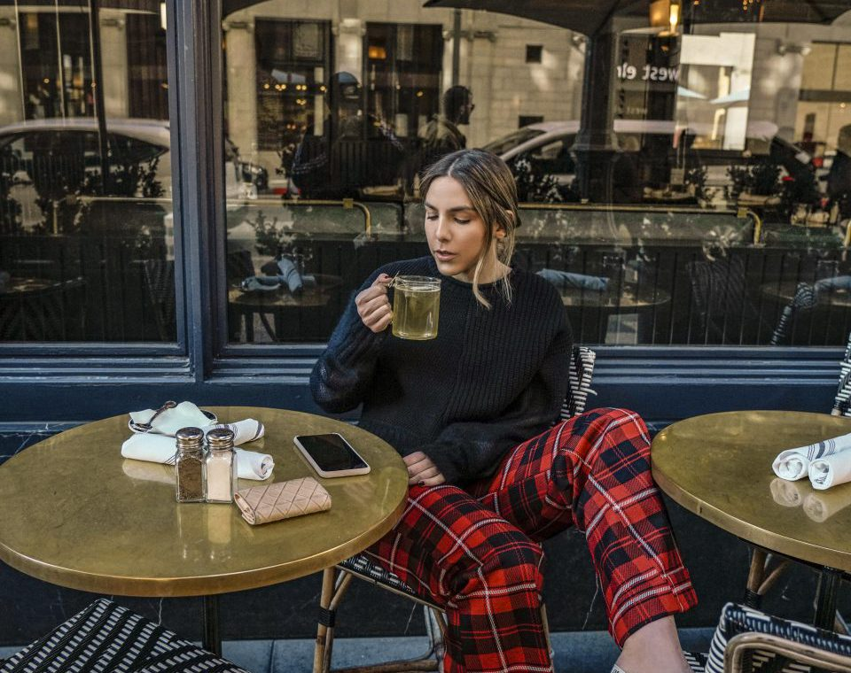 Erin sitting at a cafe table drinking tea and wearing a black long sleeve shirt and red plaid pants with pink high heels.