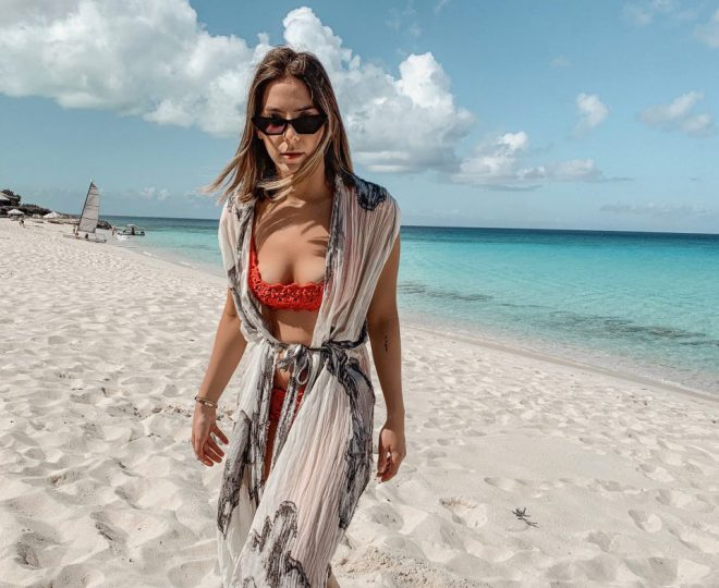 Erin walking on a sandy beach, wearing sunglasses and a bikini with a light cover dress