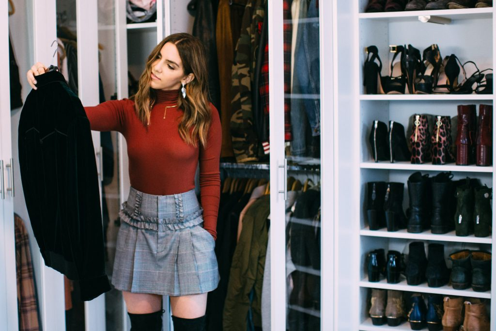 Erin standing in a well organized closet holding up a black jacket.
