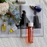 Bottles of face oil and a bouquet of flowers on top of an open magazine sitting on a knitted blanket