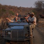 People riding in a jeep in the savanna