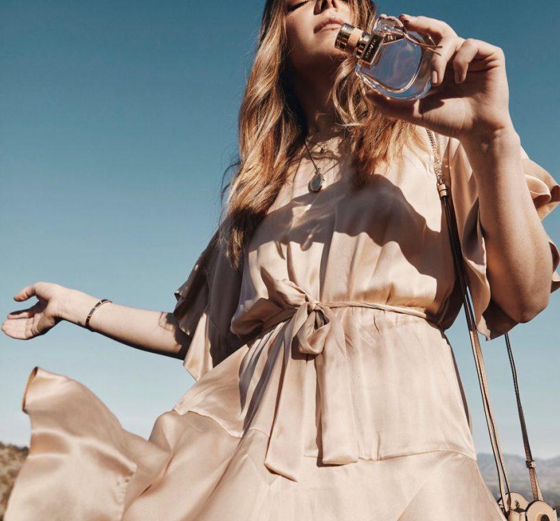 Erin holding a bottle of perfume outside