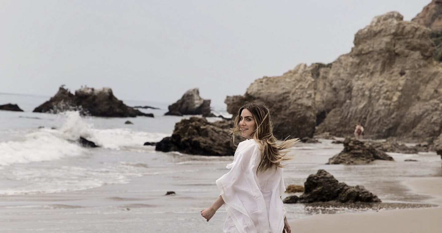 Erin walking along the beach in a white cover up, looking back over her shoulder.