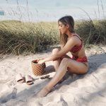 Erin sitting on the beach in a red polka dot bikini.