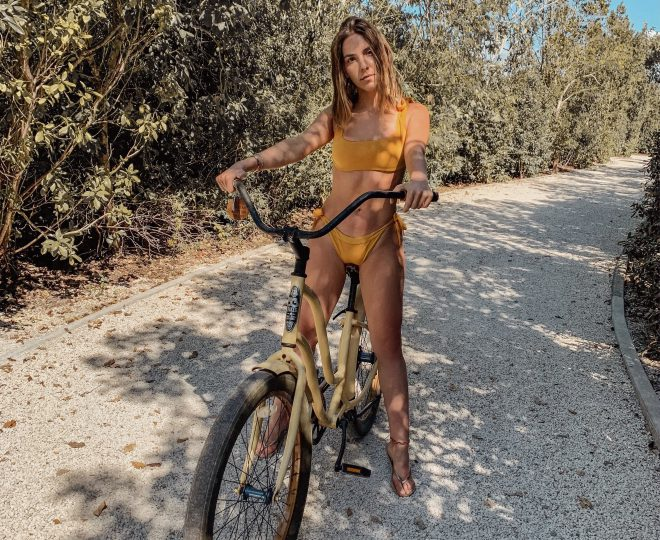 Erin in a yellow bikini sitting on a yellow bike